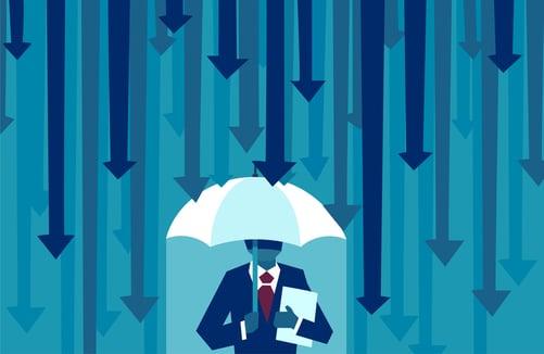 iStock-1036856344 businessman under umbrella with falling arrows