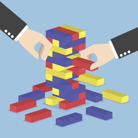 iStock-496958796 hands removing blocks like Jenga game